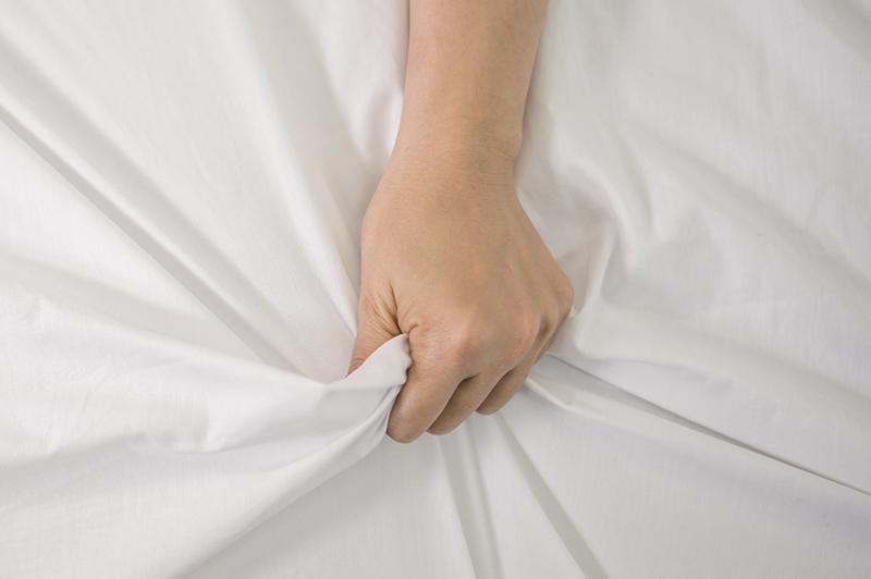 Mão de uma mulher segurando o lençol ao sentir orgasmo