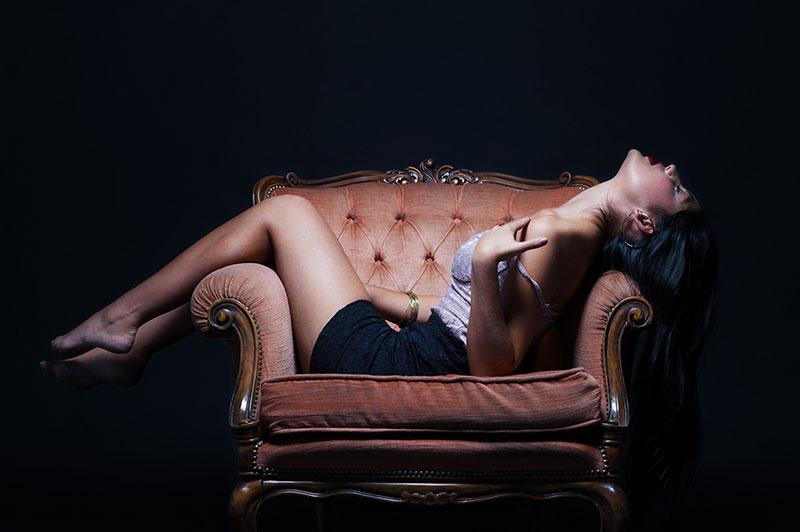 Mulher se masturbando deitada em um sofá